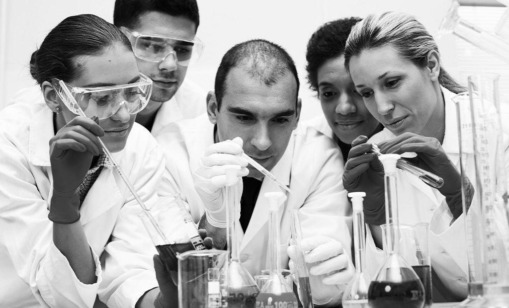 Stock photo of 5 scientist mixing random fluids
